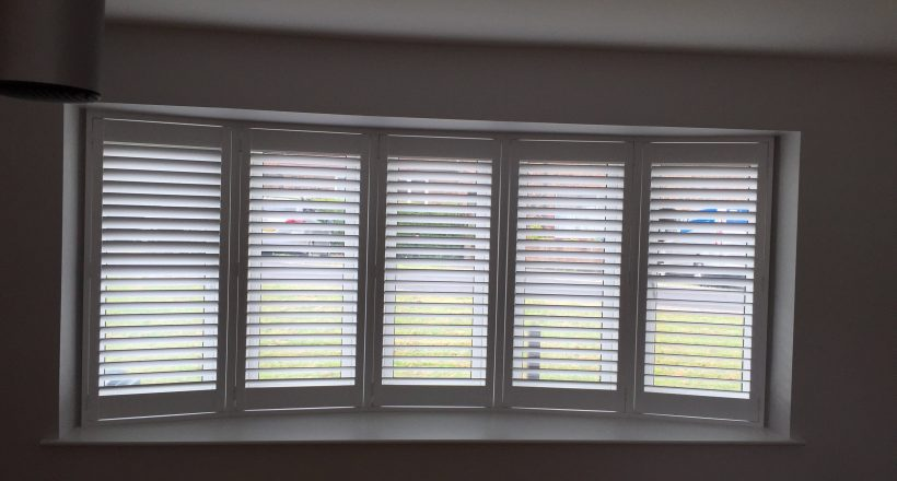 Bay window shutters one curved bay from inside house