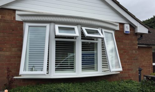 Bay window shutters seens from outside house with two large and two small windows open