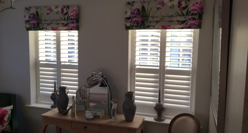 Full height Window Shutters on two windows in lounge behind roman blinds