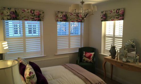 Full height Window Shutters on 3 windows in louge behind roman blinds