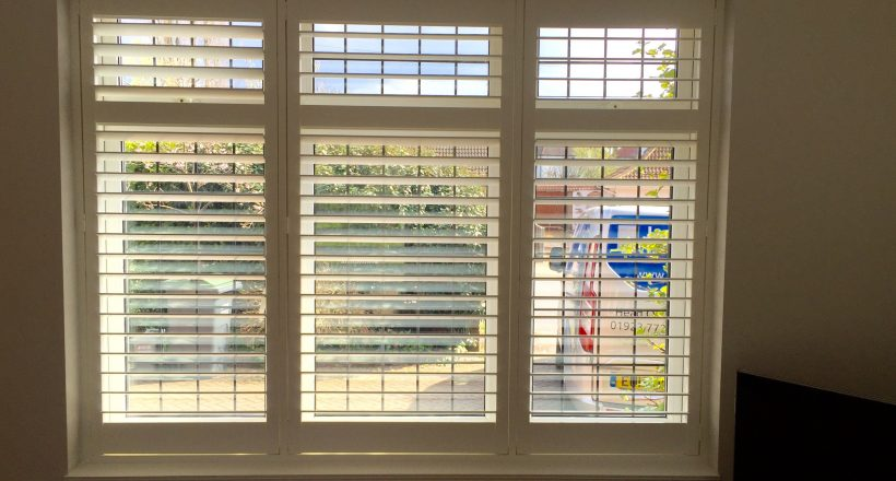 Full height window shutters on bedroom window covering all windows