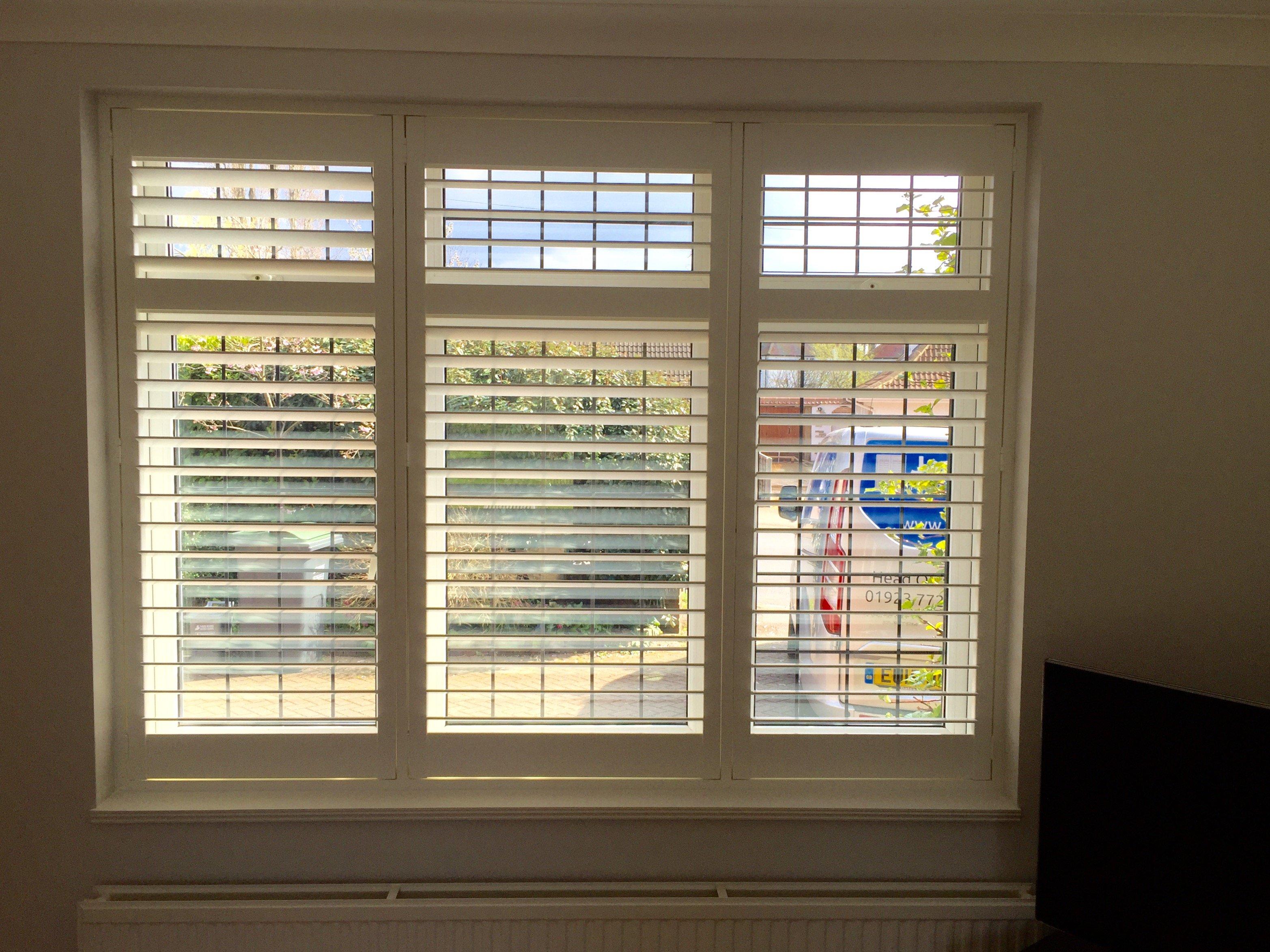 Full height window shutters on bedroom window covering all windows