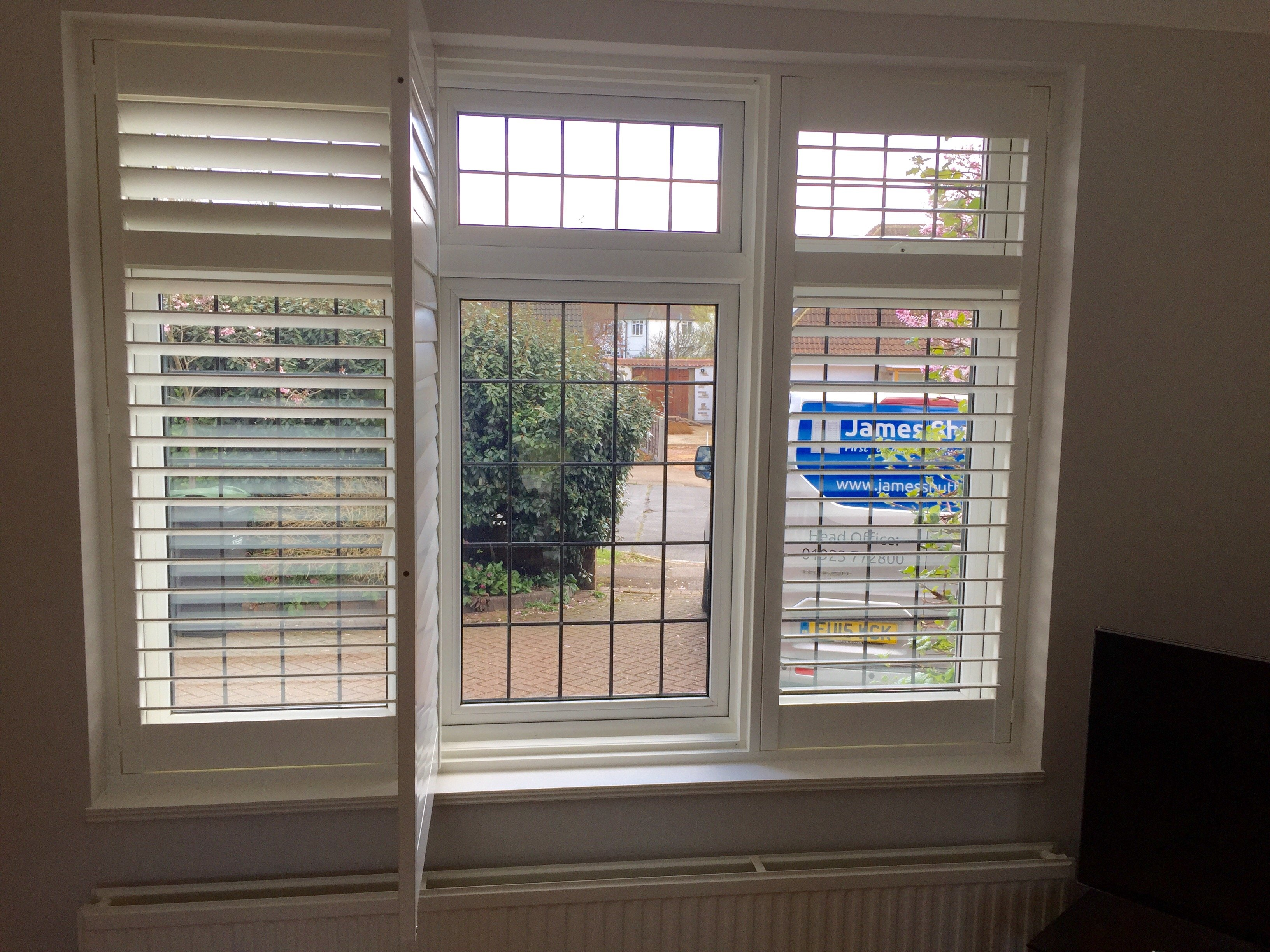 Full height Window Shutters on bedroom window with middle shutter drawn back to show windoe