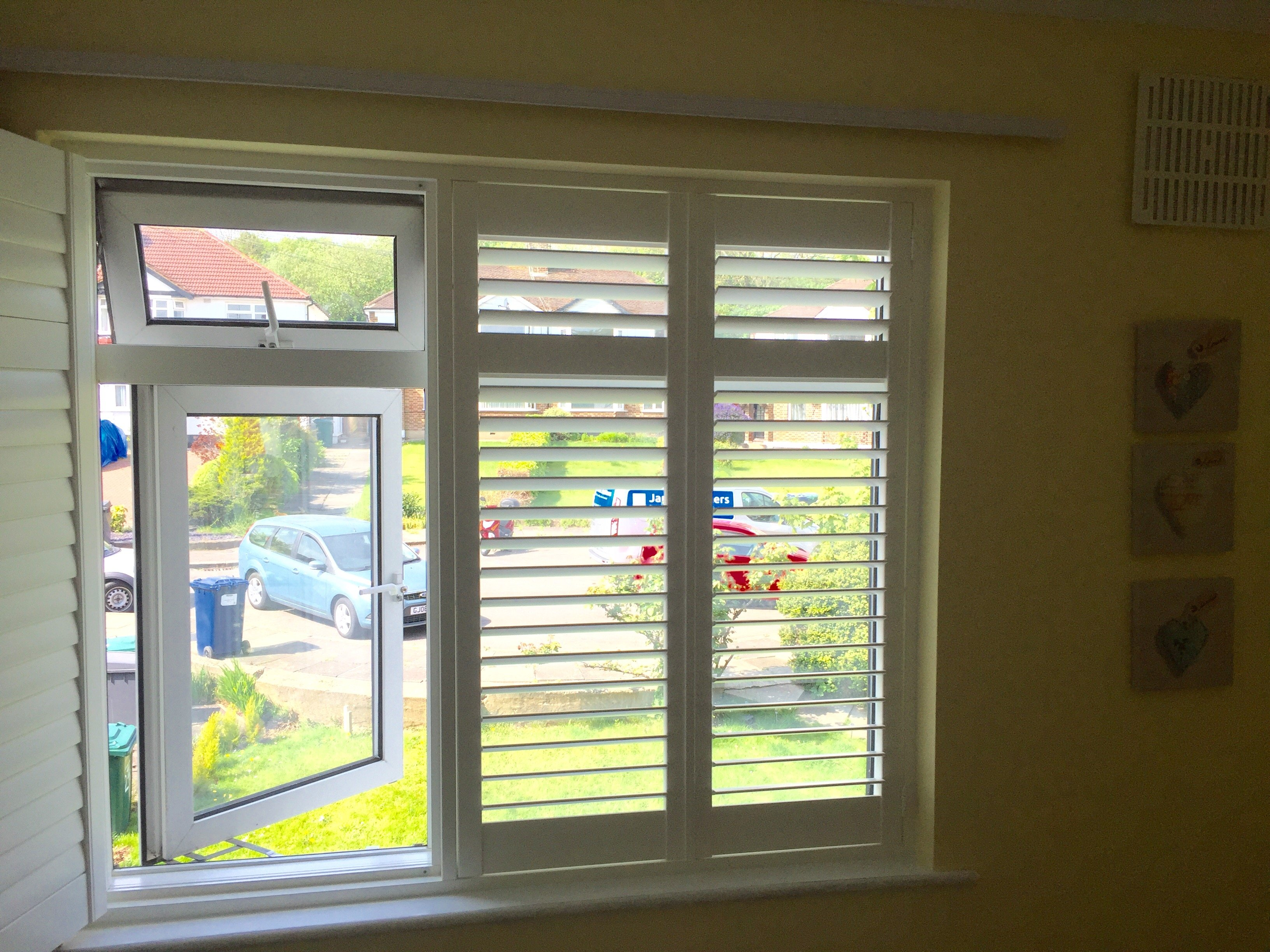 Full height Window Shutter on bedroom window with shutter pulled back to show open window and garden