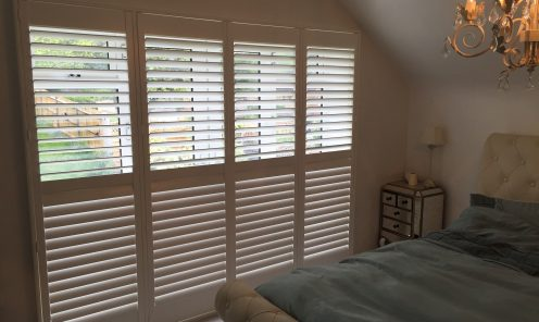 Fulll height Window Shutters along bedroom wall