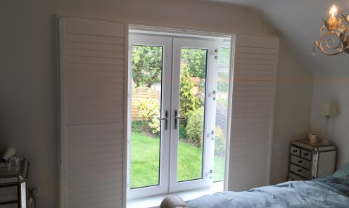 Full height window shutters pulled back to show patio doors to garden