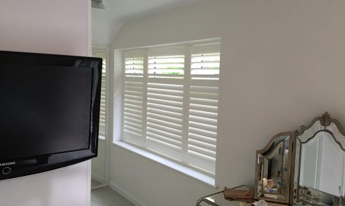 Full height white window shutters in bedroom