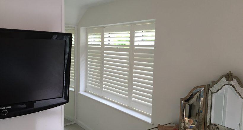Full height white window shutters in bedroom